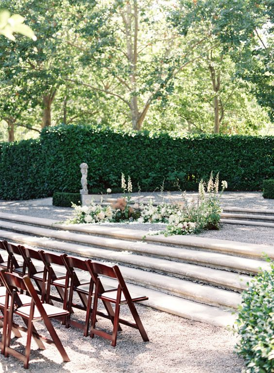 a chic garden wedding altar with some neutral blooms and greenery up the steps and a greenery wall