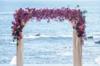 06 a colorful beach wedding arch with fuchsia and pink blooms and airy fabric for decor