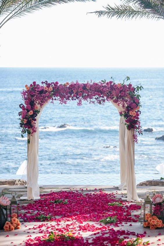 a colorful beach wedding arch with fuchsia and pink blooms and airy fabric for decor