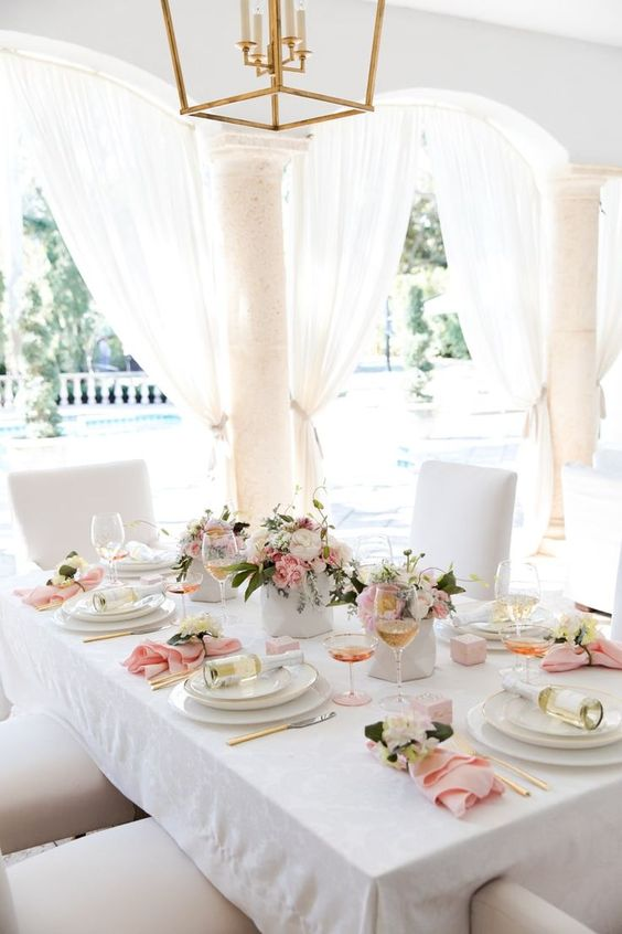 a super elegant tablescape with light pink and gold touches plus fresh blooms and greenery, little wine bottles as favors