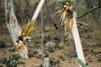 06 a triangle wedding arbor decorated with bold blooms, dried tropical leaves, herbs and succulents for a desert feel