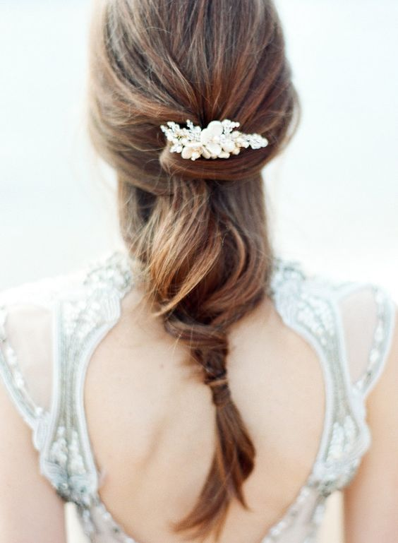 a twisted and relaxed bridal ponytail with a pearly hairpiece for a beach bride
