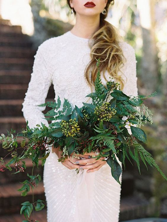 a very textural and a bit cascading wedding bouquet of greenery and some berries for a tropical bride