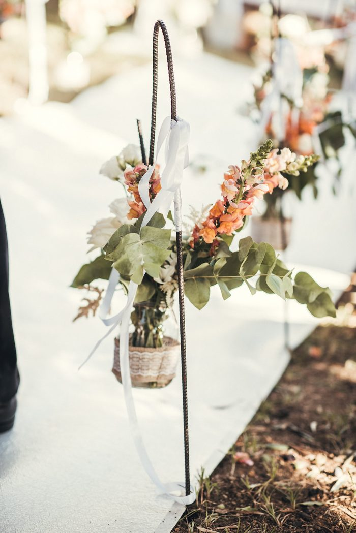 The aisle was lined with a fabric runner and fresh blooms and greenery in jars