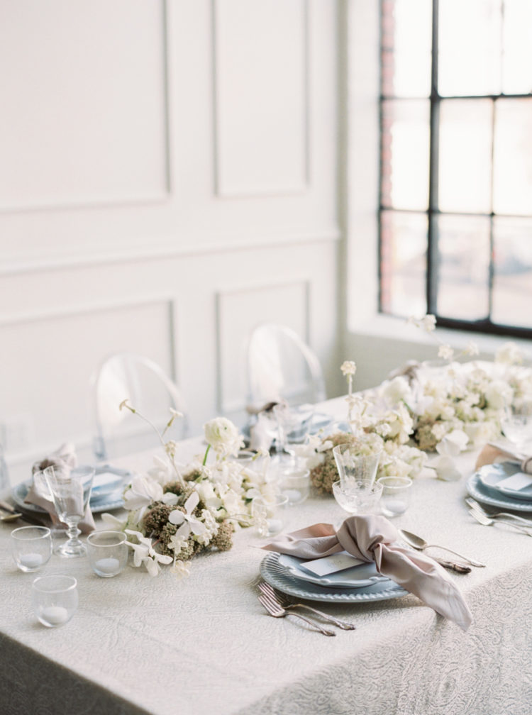 The wedding table was done with blue plates, blush napkins, candles and white floral centerpieces