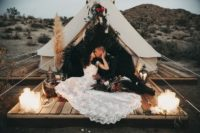 07 There was a teepee styled for the couple, with grass, greenery and blooms and a small deck with candles, lanterns and antlers