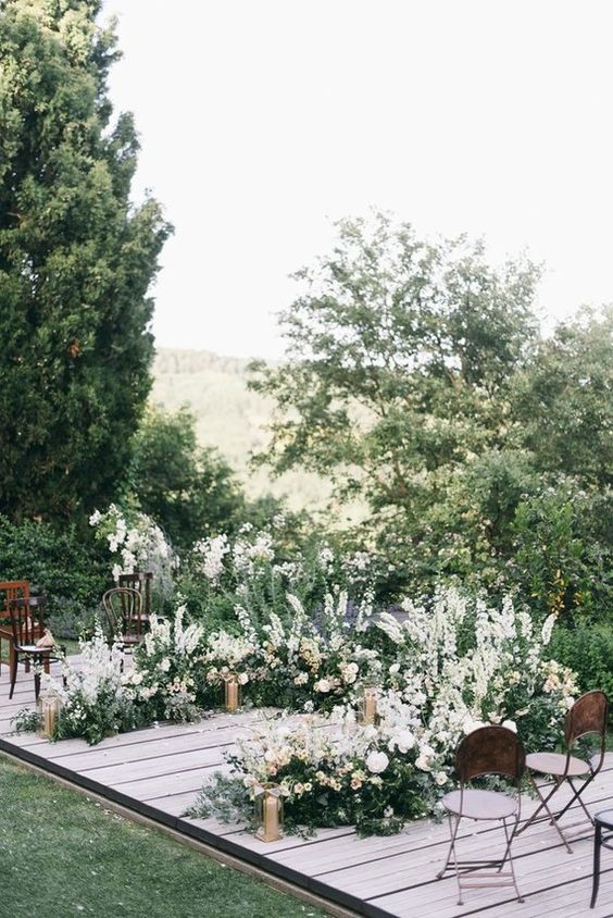 a chic wedding altar with white and blush blooms and much greenery plus gold candles on a deck