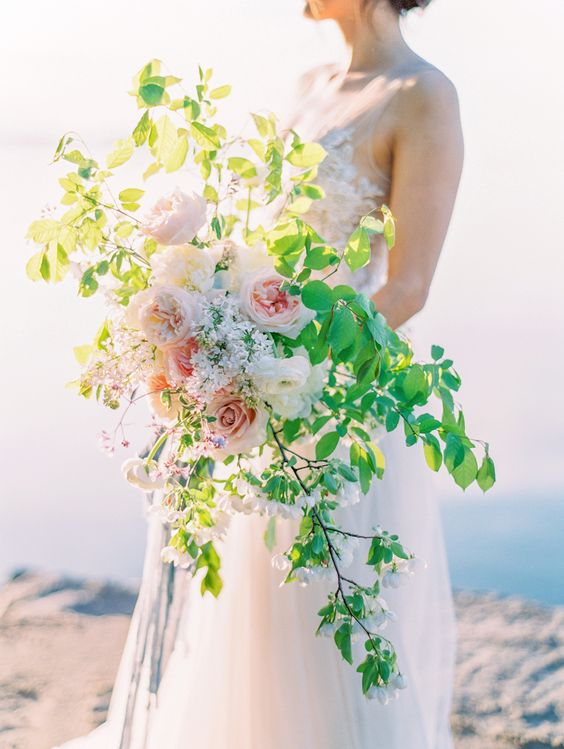 a creative textural wedding bouquet with bold greenery and some blush peonies