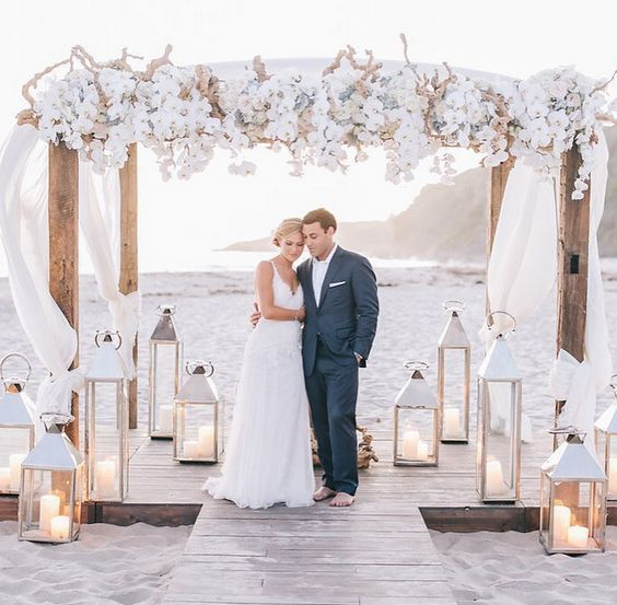 a lush wedding arch with airy white fabric, driftwood and white orchids looks very refined and chic