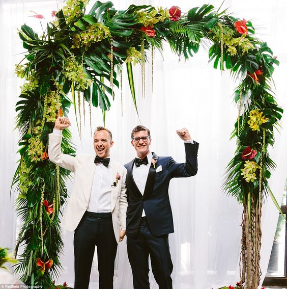 a lush wedding arch with textural greenery and yellow and red blooms
