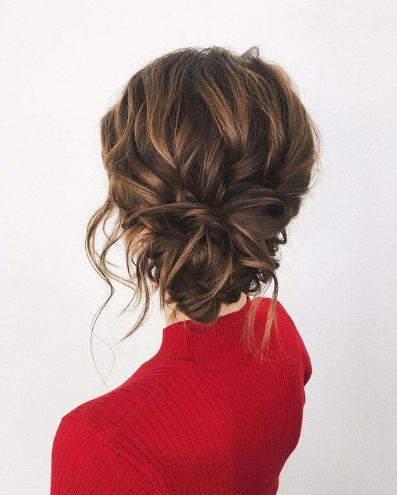 a messy wavy updo with a low twsited bun, some locks down and a volume on top