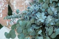 07 a pale green cascading wedding bouquet with eucalyptus, succulents and blue thistles for a fairy-tale feel