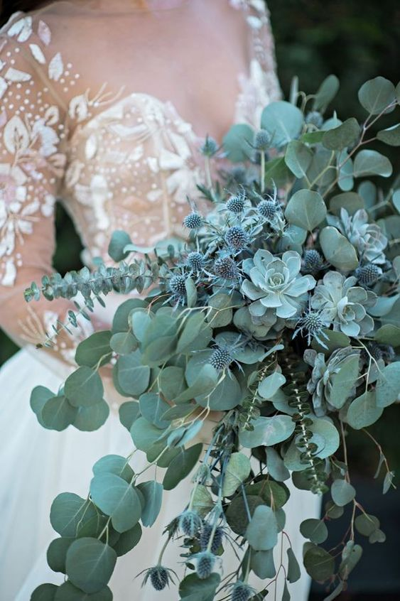 a pale green cascading wedding bouquet with eucalyptus, succulents and blue thistles for a fairy-tale feel