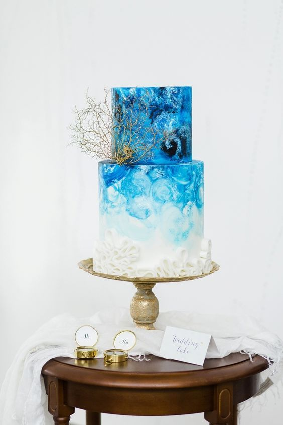 a very bold watercolor ombre blue wedding cake with a croal and textures