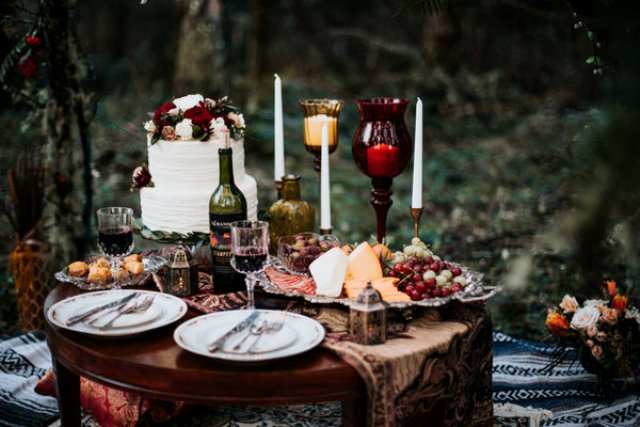 An adorable picnic setting was done with candle holders, silver flatware and candle lanterns