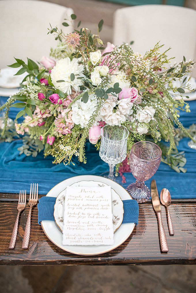 Colored glasses, blue napkins, calligraphy and rose gold flatware added a romantic feel to the table setting