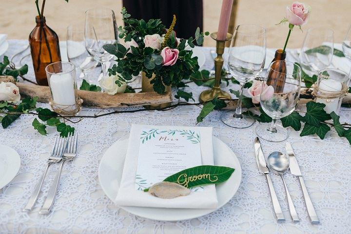 The tablescape was done with candles, driftwood, greenery, blooms and a white lace tablecloth