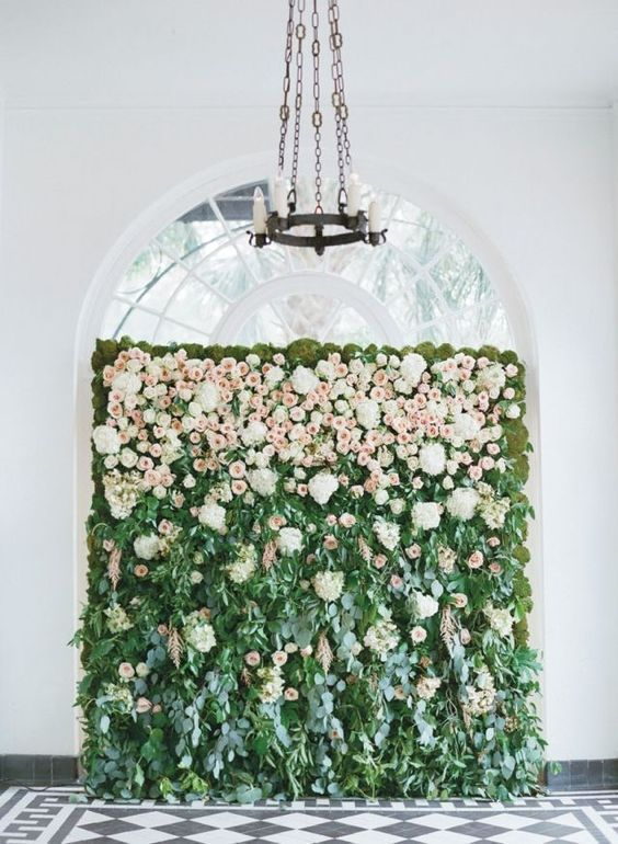 a lush greenery wall with some creamy and blush blooms on top to make your ceremony space feel like a garden