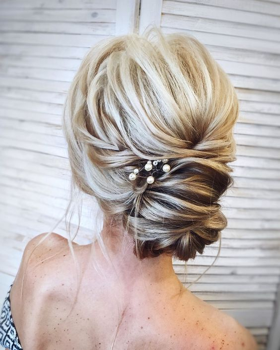 a messy twisted updo with pearl pins is a delicate idea for a romantic girl