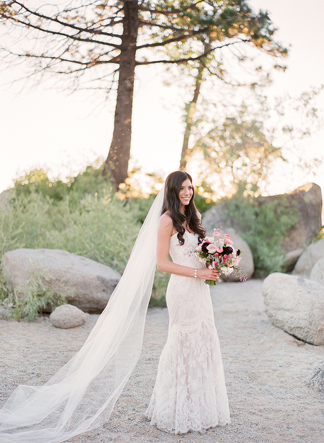 a romantic lace strapless wedding gown and a long veil for a chic and tender bridal look