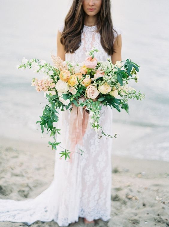 a soft-colored wedding bouquet with cascading greenery, peachy and blush blooms for a pastel touch