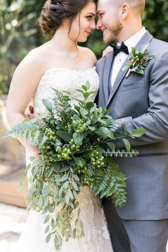 a textural and a bit cascading greenery bridal bouquet with berries for a catchy modern look