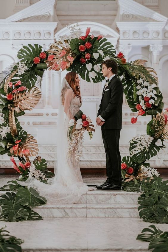 a tropical wedding arch with gilded monstera leaves, white orchids and king proteas