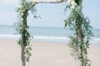 08 a whitewashed driftwood wedding arch with greenery and white and blue blooms on the beach