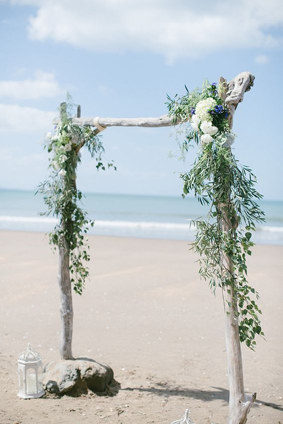 a whitewashed driftwood wedding arch with greenery and white and blue blooms on the beach