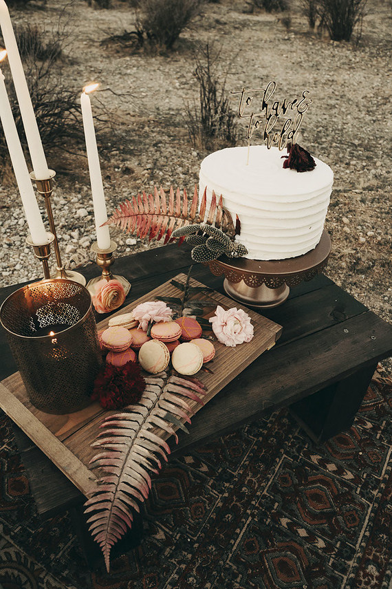 A small picnic table included a wooden tray with macarons, candles and a buttercream cake decorated with cacti