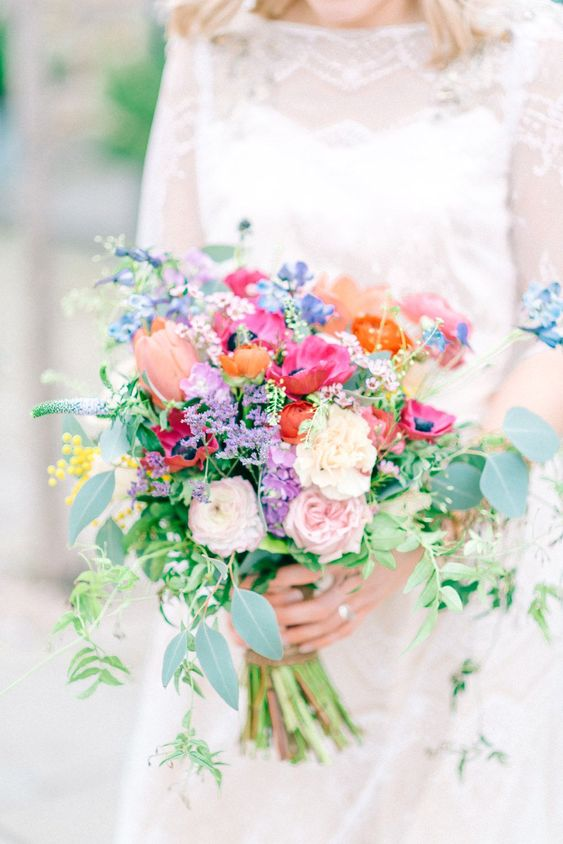 a cute wedding bouquet in fuchsia, blush, orange and purple shades and textural greenery shows off a mix of muted and bold tones
