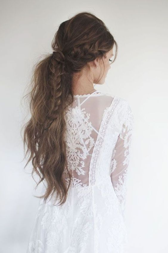 a low messy ponytail with a braid is ideal for a boho chic bride