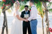 09 a lush and colorful tropical wedding arch of driftwood, tropical greenery and pink and orange blooms