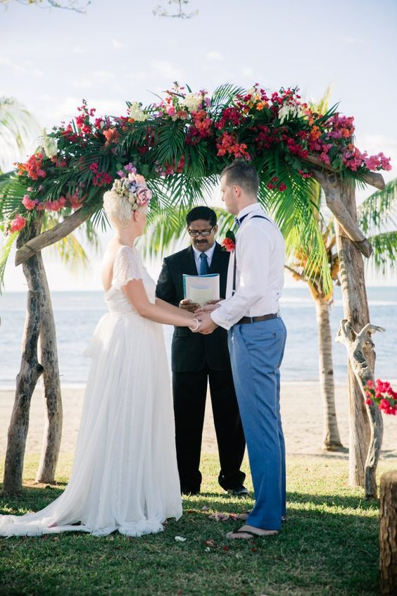a lush and colorful tropical wedding arch of driftwood, tropical greenery and pink and orange blooms