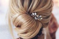 09 a messy low chignon hairstyle with some volume on top, locks down and a little rhinestone hairpiece