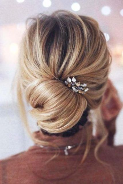 a messy low chignon hairstyle with some volume on top, locks down and a little rhinestone hairpiece