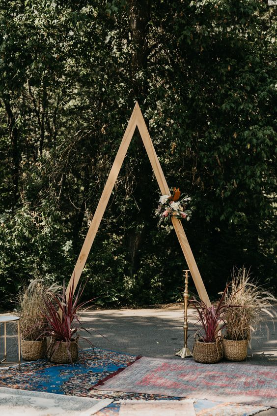 a wooden wedding arch with a floral and leaf decoration and various dried herbs in wickr pots