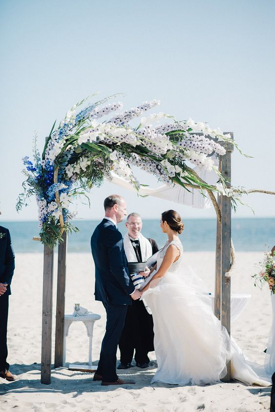 an aged wood wedding arch with breezy flower decor in blue, white and lilac blooms