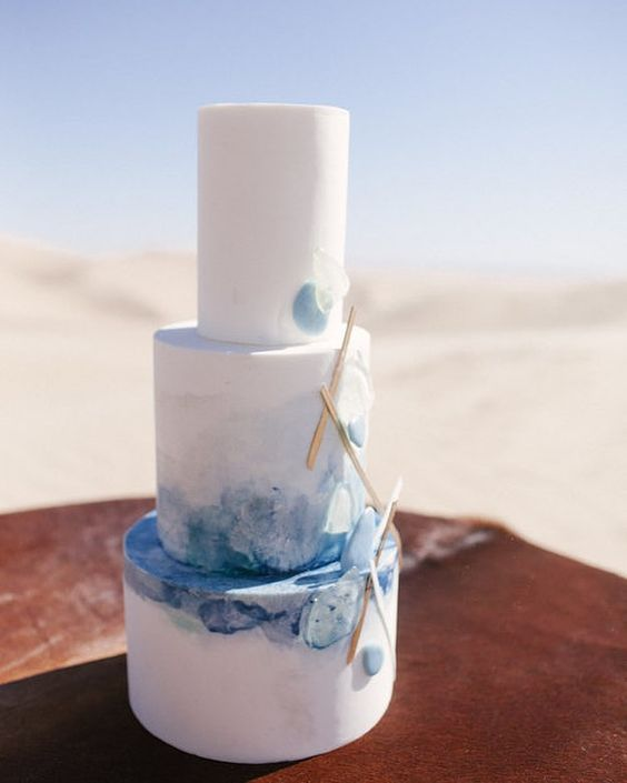 gorgeous beach wedding cake decorated with blue watercolor, seaglass and driftwood, all of them are edible