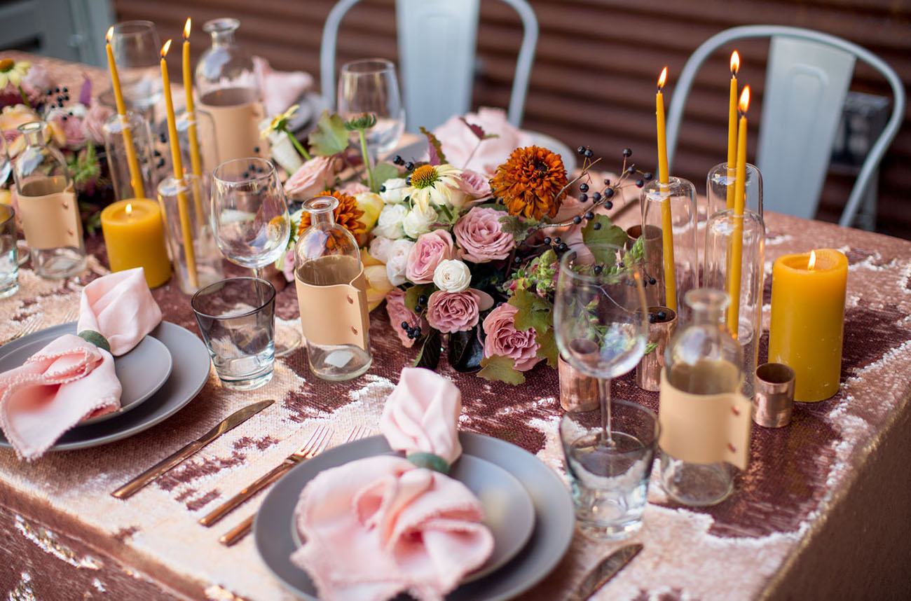 The wedding tablescape was done with pink sequins, pink and rust blooms, mustard candles and grey plates