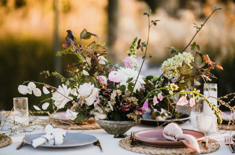 The wedding tablescapes were done with lush and textural centerpieces, matte plates and woven chargers
