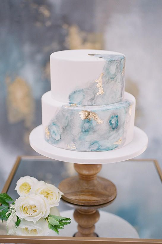 a beach wedding cake with light blue watercolor and gold leaf for a romantic feel