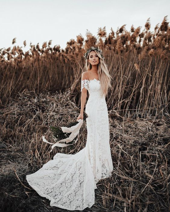 a boho lace off-the-shoulder wedding dress with a train is ideal for a boho chic bride