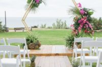 10 a hexagon tropical wedding arch decorated with lush greenery and fuchsia blooms