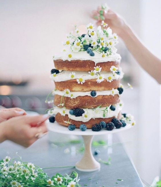 a naked summer cake with daisies, blueberries and blackberries for a boho or country summer wedding