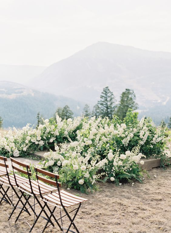 a very lush greenery and white bloom wedding altar up the steps with a cool mountain backdrop view