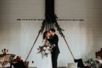 10 a wooden triangle wedding arch topped with fresh greenery and with a macrame backdrop behind for a boho feel