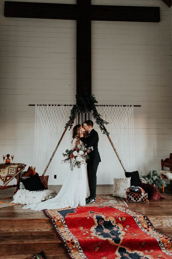 a wooden triangle wedding arch topped with fresh greenery and with a macrame backdrop behind for a boho feel