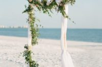 10 an organic wedding arch with airy fabric, greenery and blush blooms