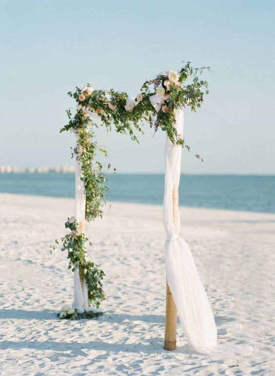 an organic wedding arch with airy fabric, greenery and blush blooms
